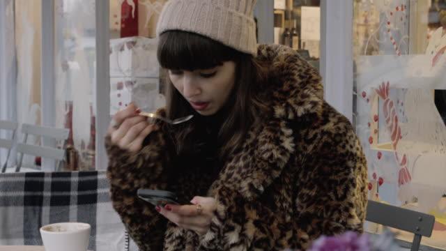 vídeos y material grabado en eventos de stock de woman drinks coffee while looking at phone in outdoor seating area of cafe. - esmalte de uñas rojo