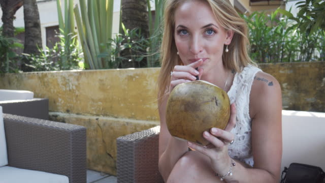 Woman drinks from coconut