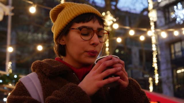stockvideo's en b-roll-footage met woman drinks hot chocolate at christmas market. - stadsreis