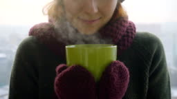 Woman drinks hot tea or coffee from green cup on winter morning