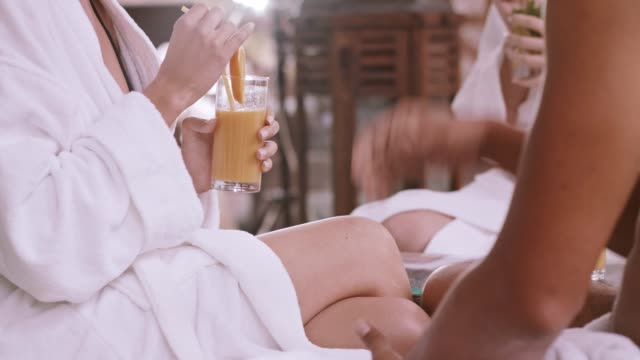 woman drinks orange juice at spa - bathrobe stock videos & royalty-free footage