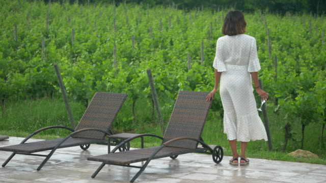 A woman drinks white wine while traveling at a luxury resort in Italy, Europe. - Slow Motion