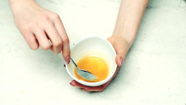 Vrouw druipend van lepel honing in kom
