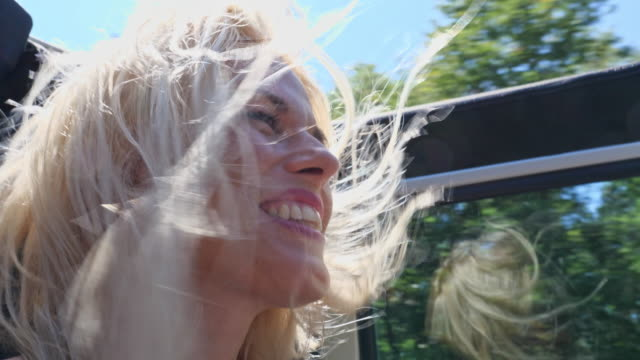 woman driver on road trip in convertible car - windswept stock videos & royalty-free footage