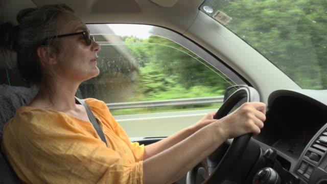 vídeos de stock, filmes e b-roll de a woman drives a car - 50 54 anos