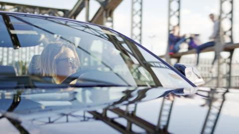 woman drives her car sharing convertible sports car over a city bridge - vorderansicht stock-videos und b-roll-filmmaterial