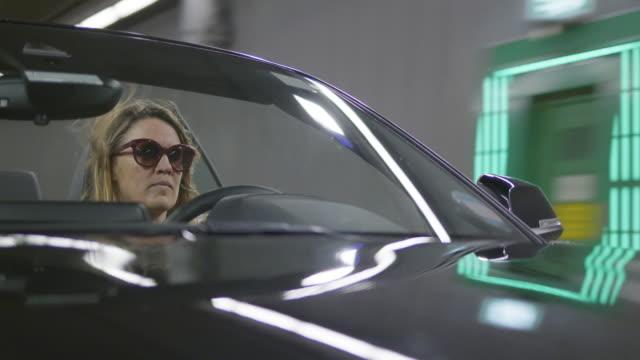 woman drives her open cabriolet in city tunnel and forgot to take off her sunglasses - independence stock videos & royalty-free footage