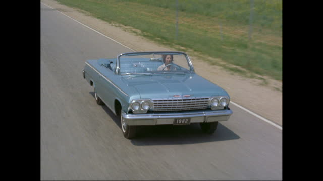 MS TS HA woman driving 1962 Chevrolet convertible car moving on road / United States