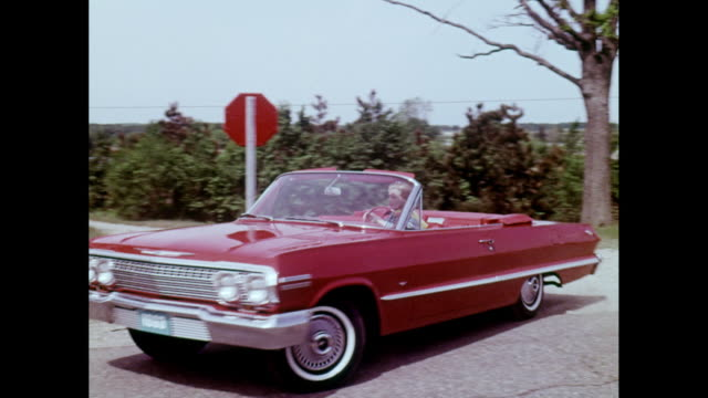 stockvideo's en b-roll-footage met ms pan woman driving 1963s chevrolet bel air on road / united states - 1963