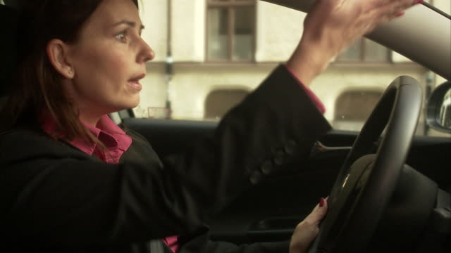 a woman driving a car sweden. - contrariato video stock e b–roll