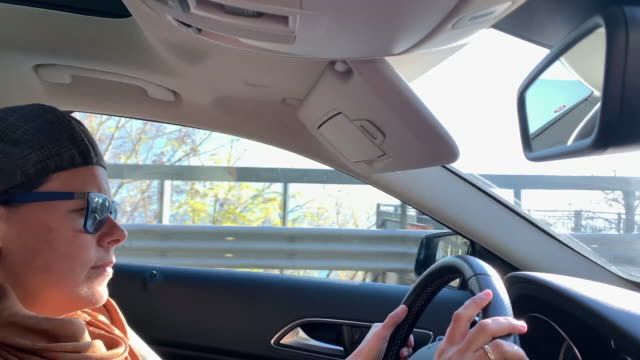 woman driving a car with sunlight - schiebermütze stock-videos und b-roll-filmmaterial