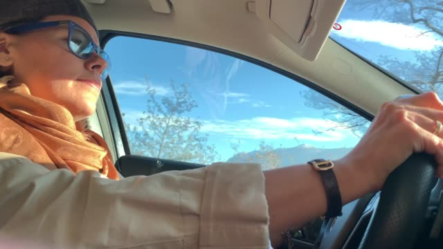 Woman Driving a Car with Sunlight