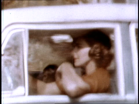 vidéos et rushes de / woman driving along in her rambler station wagon and fantasizing about the clothes she just bought / woman almost runs through an intersection and... - fantaisie