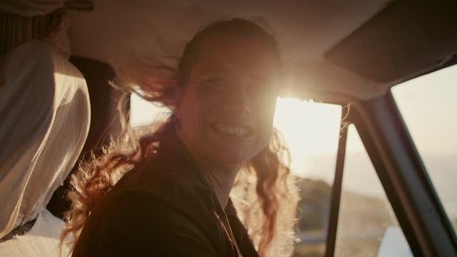 stockvideo's en b-roll-footage met woman driving at sunset, smiling - rondrijden