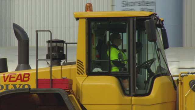 ms pan woman driving bulldozer moving pile of woodchips outside biomass plant / vaxjo, sweden - vaxjo stock videos & royalty-free footage