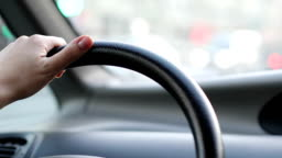 Woman driving car. Close up of steering wheel and hands.