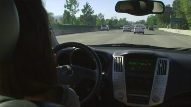 CU, Woman driving car on highway, view from back seat, Los Angeles, California, USA