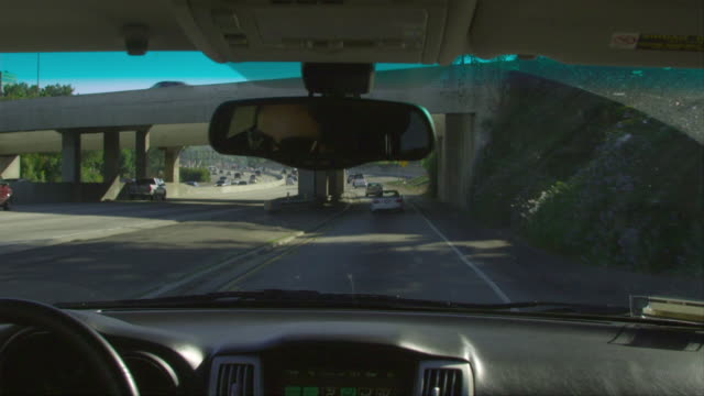 CU, PAN, Woman driving car on highway, view from back seat, Los Angeles, California, USA