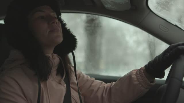 vidéos et rushes de femme conduisant la voiture le jour d'hiver - glacé