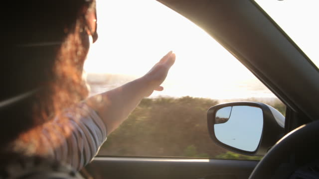 Woman driving car, she puts her hand out of window to feel the breeze.