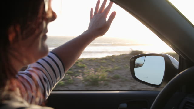 woman driving car, she puts her hand out of window to feel the breeze. - car interior stock videos & royalty-free footage