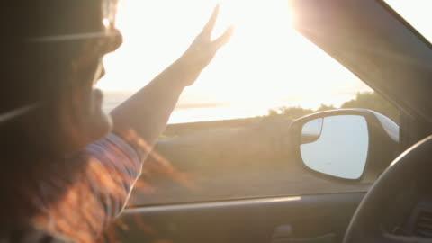 vídeos y material grabado en eventos de stock de woman driving car, she puts her hand out of window to feel the breeze. - coastline