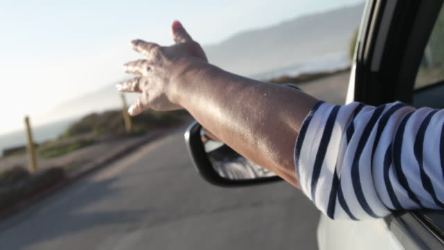 woman driving car, she puts her hand out of window to feel the breeze. - waving hands stock videos & royalty-free footage