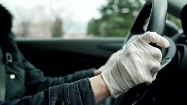 vídeos de stock e filmes b-roll de woman driving car with protective gloves - europe