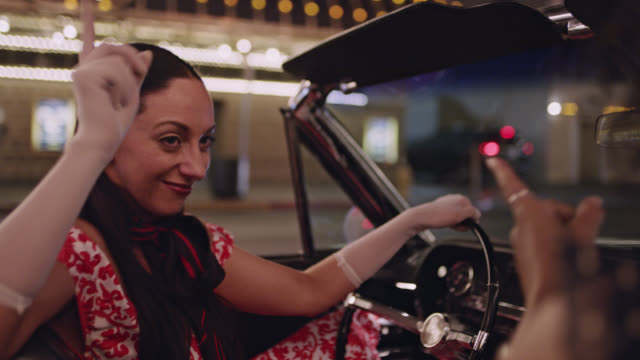 Woman driving classic convertible waves to crowd and dances and sings with friend on girls night out in Las Vegas.
