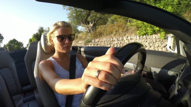 woman driving convertible car. in vehicle close-up. - convertible stock videos & royalty-free footage