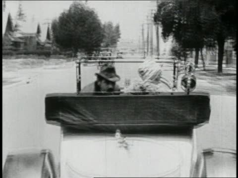 b/w 1923 rear view woman driving convertible + looking behind her / large man sits up / feature - 1923 stock videos & royalty-free footage
