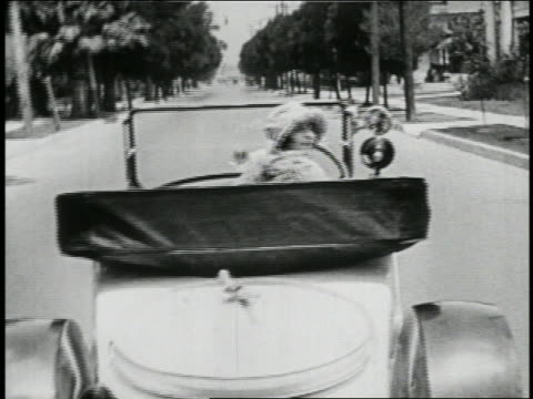 b/w 1923 rear view woman driving convertible looking behind her + waving / feature - 1923年点の映像素材/bロール