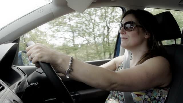 vidéos et rushes de femme conduire une voiture familiale au ralenti - 4x4