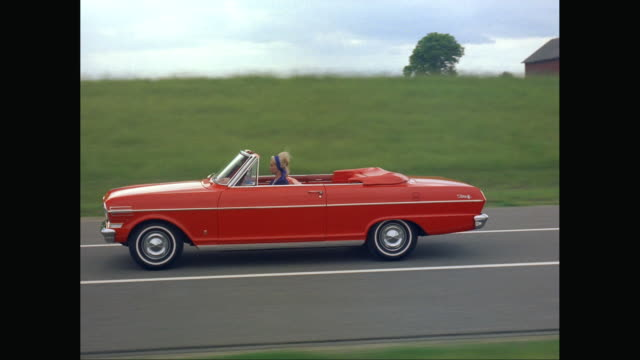 ws ts woman driving red convertible car through countryside / united states - クラシックカー点の映像素材/bロール