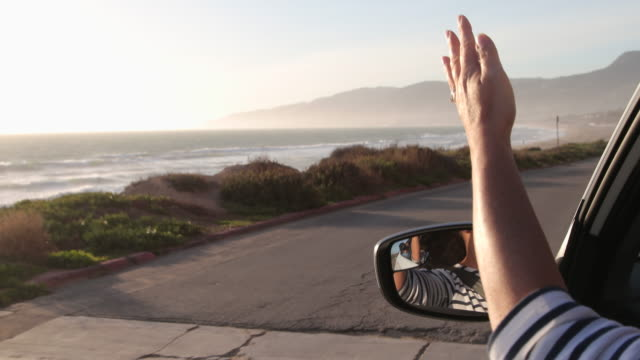 woman driving with arm out of window feeling the breeze. - waving hands stock videos & royalty-free footage