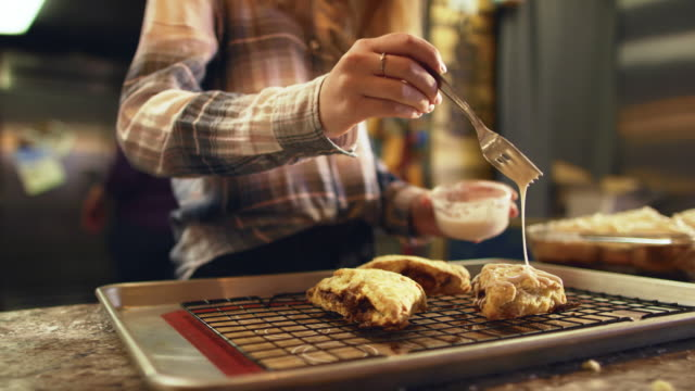 a woman drizzles icing on to homemade scones in a bakery - baking tray stock videos & royalty-free footage