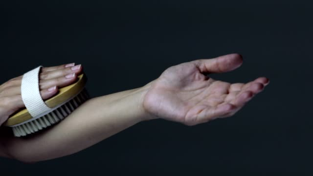 woman dry brushing her arm to peel dead skin off - brushing stock videos & royalty-free footage