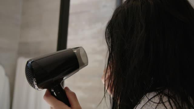 vidéos et rushes de cheveux de séchage de femme dans la salle de bains - cheveux mouillés