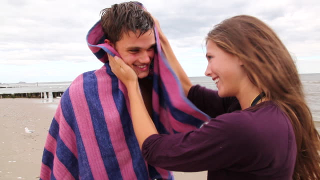 vidéos et rushes de ms zo woman drying man hair with towel on beach / rockaway, new jersey,united states - sécher activité