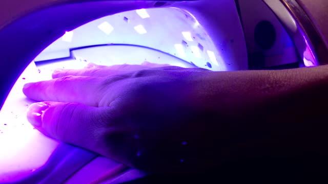 vídeos de stock e filmes b-roll de woman drying nail polish inside a uv lamp in spa salon. - lâmpada elétrica