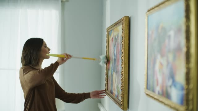 Woman dusting frames of paintings on wall / Cedar Hills, Utah, United States