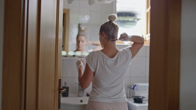woman dyeing hair in front of a mirror in the bathroom - dye stock videos & royalty-free footage