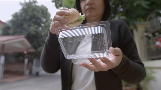 kvinna äta hamburgare från plastic box slow motion - slit och släng bildbanksvideor och videomaterial från bakom kulisserna