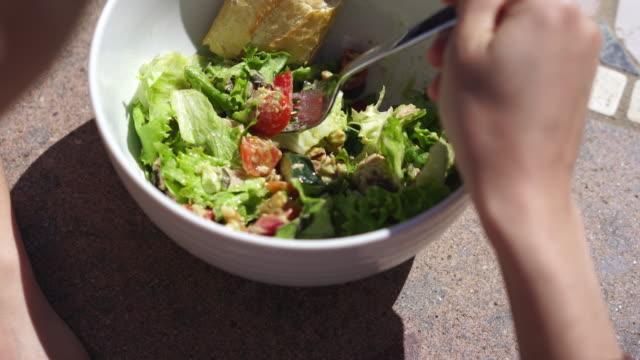 vídeos de stock e filmes b-roll de woman eating a caesar salad with bred - tigela