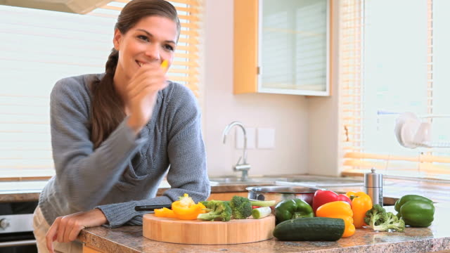 Woman eating a piece of pepper