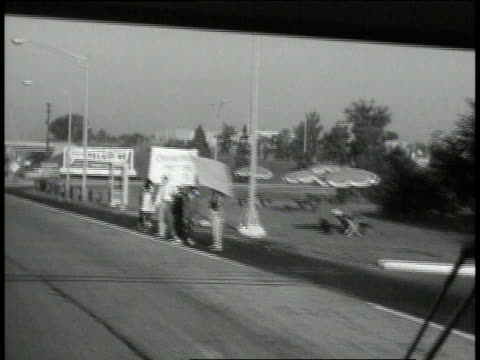 vídeos de stock e filmes b-roll de woman eating a sandwich / onlookers waving signs on the sides of the road as bus passes / passenger riding on bus - 1963