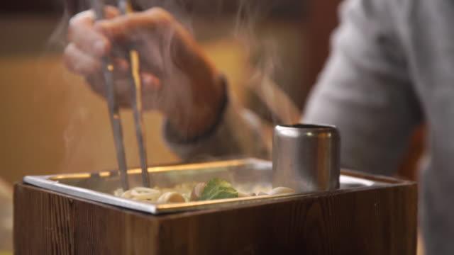 Woman eating a Shabu Shabu meal at Japanese restaurant