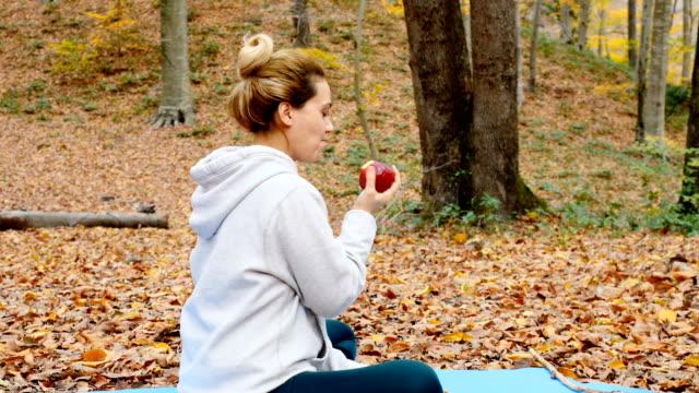 vídeos y material grabado en eventos de stock de mujer comiendo una manzana en el bosque - manzana