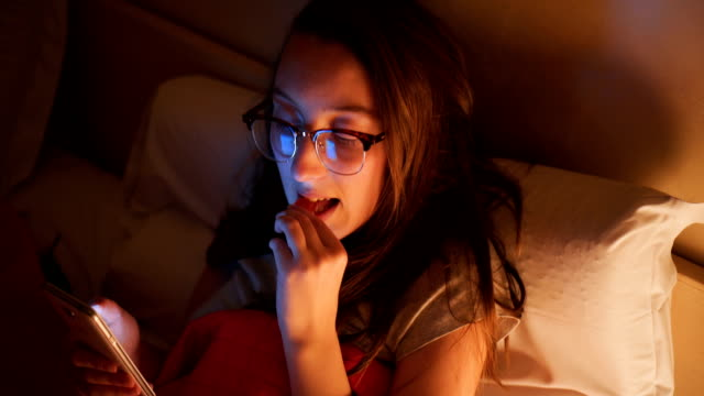 vídeos de stock e filmes b-roll de woman eating and using phone in the bed - lanche