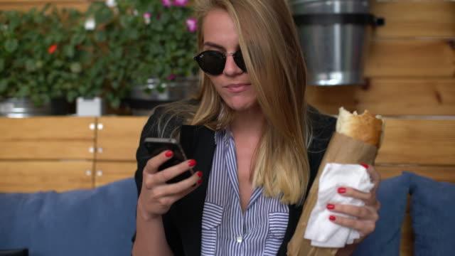 woman eating and using phone - panino ripieno video stock e b–roll